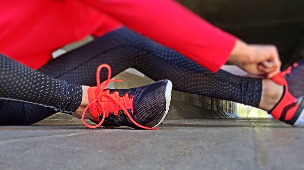 Woman in red exercise gear tying shoelaces before workout